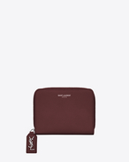 SAINT LAURENT Rive gauche SLG D RIVE GAUCHE Compact Zip Around Wallet with Monogrammed Pull in Dark Red Grained Leather  f